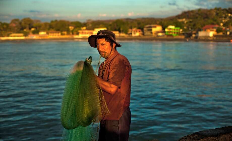 El Salvador: A fisherman holds his net in La Libertad, 35 km south of San Salvador, El Salvador on February 23, 2014. The fishing industry has grown some 45% in the last 15 years in Central America. Photo: JOSE CABEZAS, AFP/Getty Images