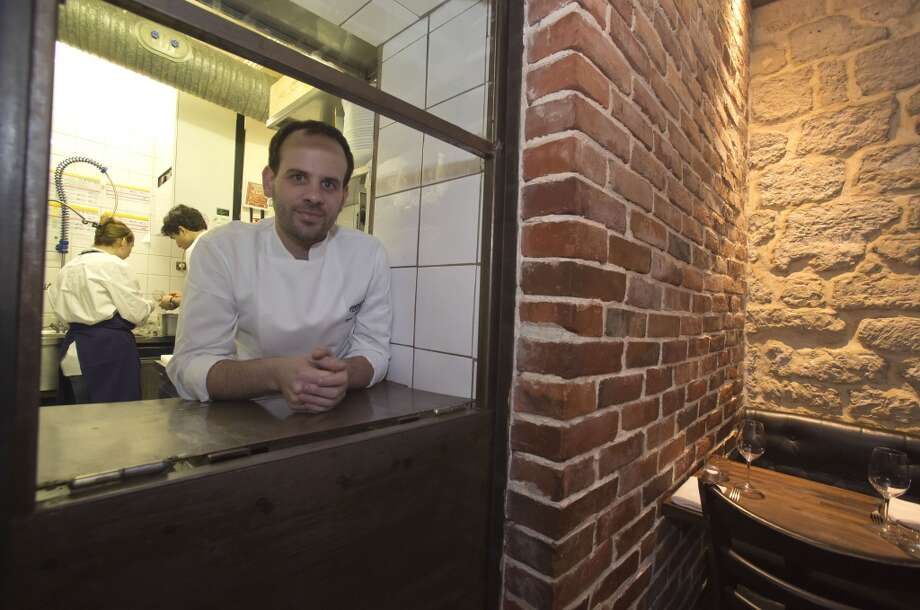 France: Chef Greg Marchand stands behind the waiter's window in his restaurant Frenchie in Paris. Photo: Michel Euler, Associated Press