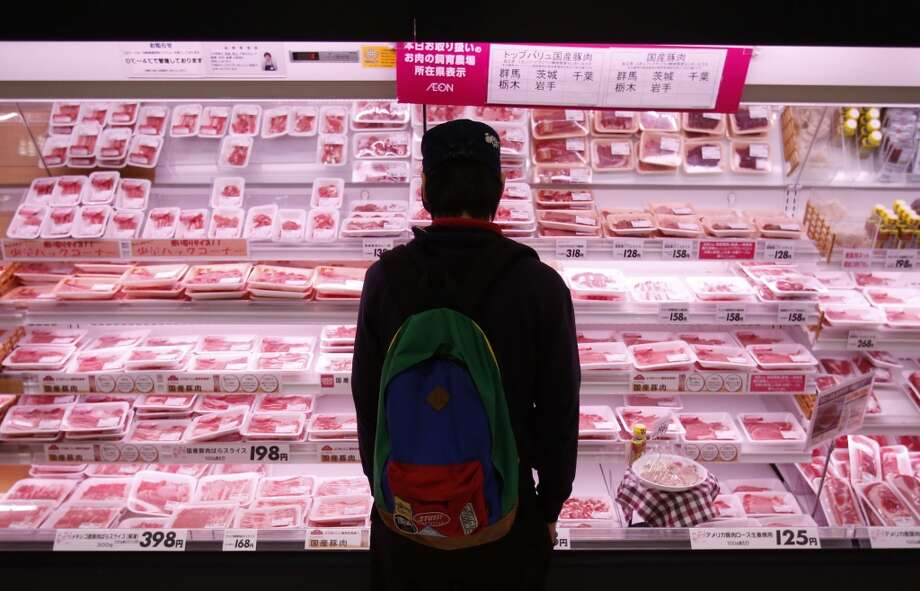 Japan: A shopper browses packs of meat products at a supermarket in Chiba, east of Tokyo. Photo: YUYA SHINO, Reuters