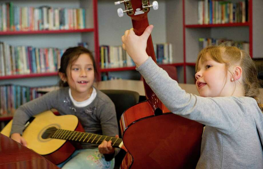 Mariya Pychil, 6, front, shows Dania Pinto, 8, a chord as they practice guitar during a lesson at the Boys and Girls Club of Stamford on Friday, March 14, 2014. Photo: Lindsay Perry / Stamford Advocate