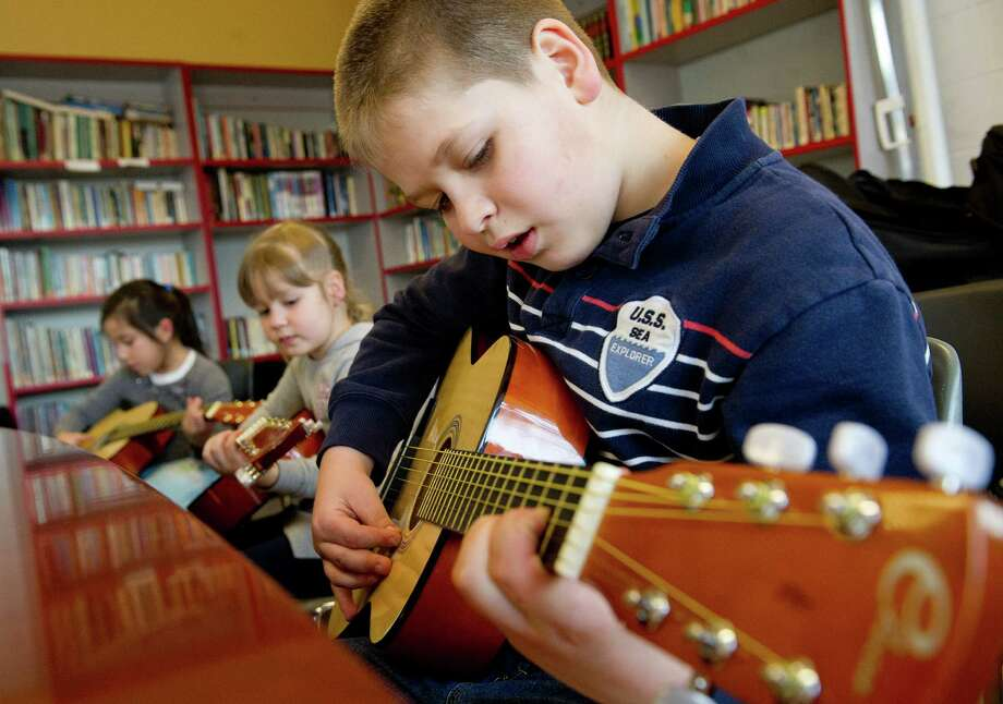 From front, Roman Pychil, 9, his sister, Mariya, 6, and Dania Pinto, 8, practice guitar during a lesson at the Boys and Girls Club of Stamford on Friday, March 14, 2014. Photo: Lindsay Perry / Stamford Advocate