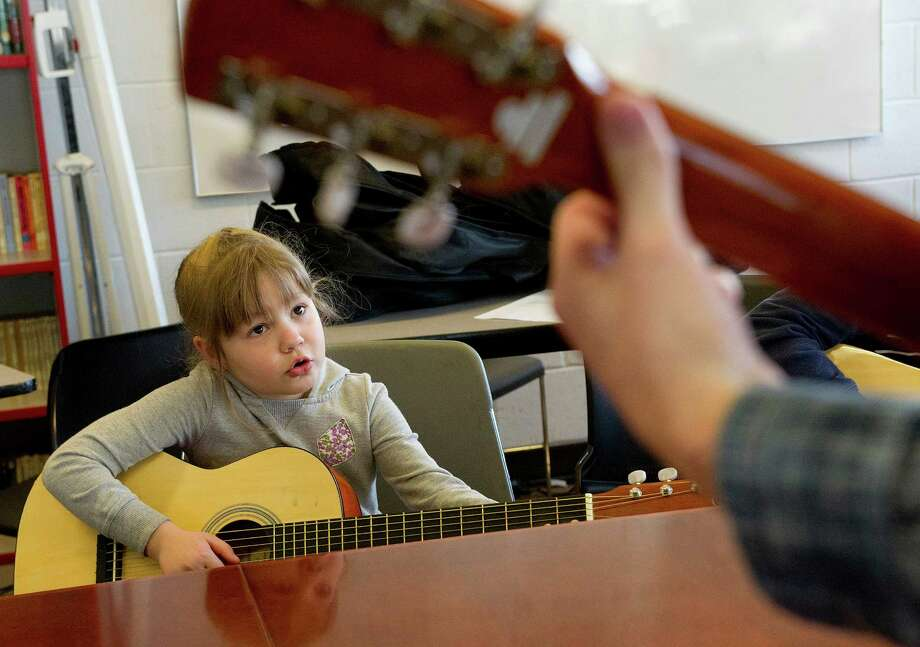 Mariya Pychil, 6, practices guitar during a lesson at the Boys and Girls Club of Stamford on Friday, March 14, 2014. Photo: Lindsay Perry / Stamford Advocate
