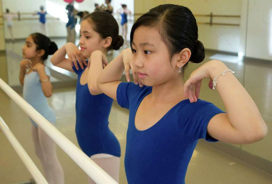 Charleen You, far right, practices ballet during a lesson at The Ballet School of Stamford on Thursday, March 14, 2014. The school is a recipient of a grant from the Community Arts Partnership Program. Photo: Lindsay Perry / Stamford Advocate