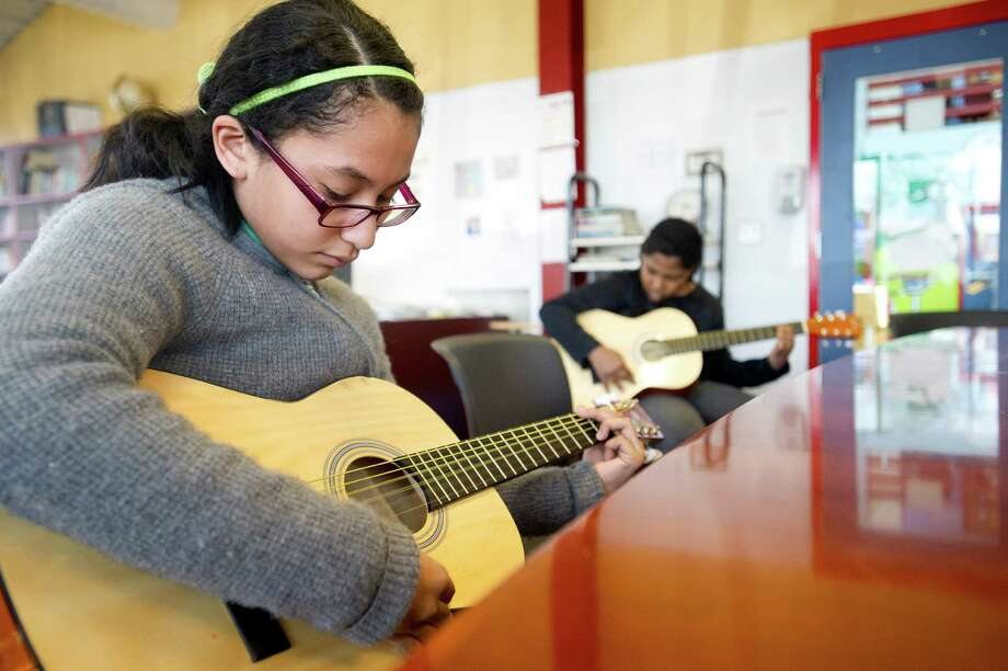 Dulce Cabrera practices guitar during a lesson at the Boys and Girls Club of Stamford on Friday, March 14, 2014. Photo: Lindsay Perry / Stamford Advocate
