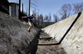 Hetch Hetchy Water and Power water operations analyst, Dr. Chris Graham, on Thursday March 13, 2014, near Groveland, Calif., crosses a section of the Lower Cherry Aqueduct which was damaged during the Rim Fire, hasn't been in operation since 1991. San Francisco and the thousands of suburban customers its water agency serves are in a pretty good spot currently as it relates to the drought, but water officials want to plan ahead. So the San Francisco Public Utilities Commission is looking into the possibility of diverting water into the Lower Cherry Aqueduct below Cherry Lake and eventually joining the Hetch Hetchy water supply.