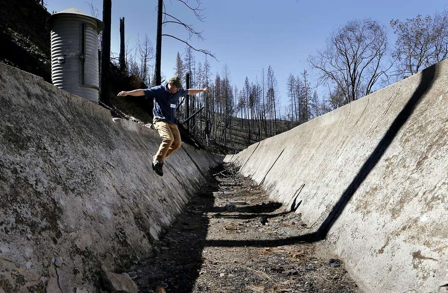 Hetch Hetchy Water and Power water operations analyst, Dr. Chris Graham, on Thursday March 13, 2014, near Groveland, Calif., crosses a section of the Lower Cherry Aqueduct which was damaged during the Rim Fire, hasn't been in operation since 1991. San Francisco and the thousands of suburban customers its water agency serves are in a pretty good spot currently as it relates to the drought, but water officials want to plan ahead. So the San Francisco Public Utilities Commission is looking into the possibility of diverting water into the Lower Cherry Aqueduct below Cherry Lake and eventually joining the Hetch Hetchy water supply. Photo: Michael Macor, The Chronicle