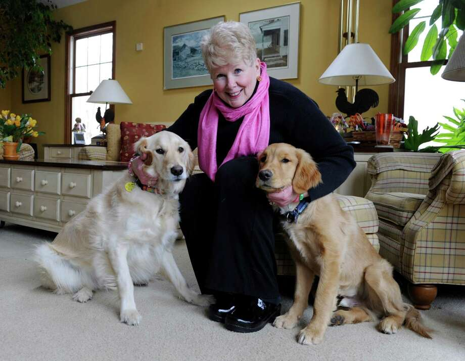 Roseanne Loring, 64, of Newtown, Conn., is photographed with her Golden retrievers, Abbey and Doolin, in her home, Friday, March 14, 2014. Photo: Carol Kaliff / The News-Times