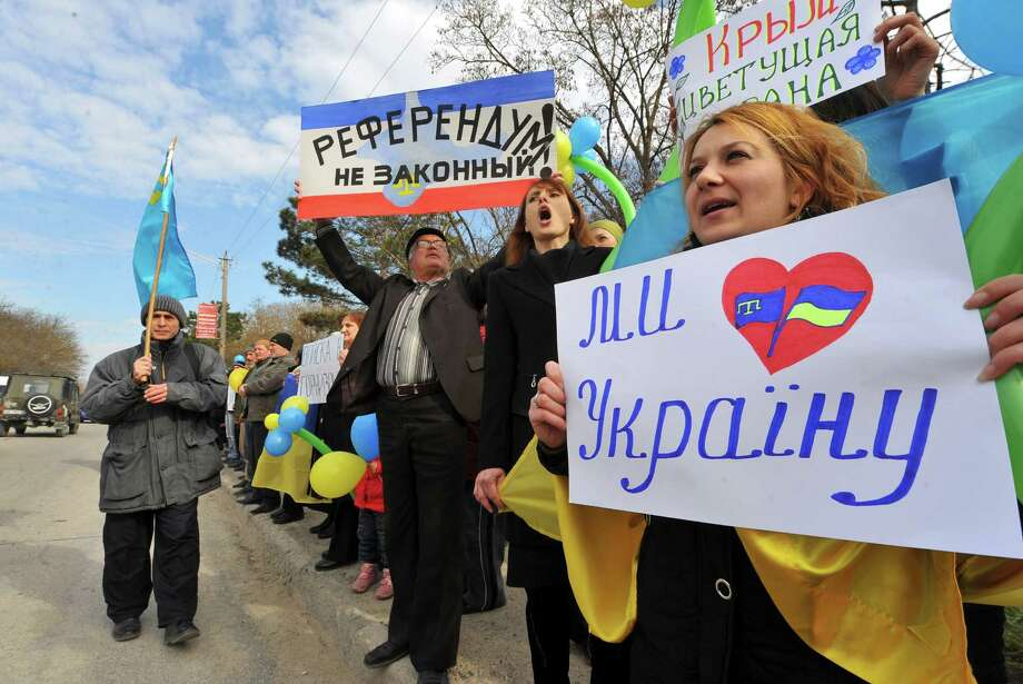 "A man holds a sign reading ""Illegal referendum"" (2nd L) and a woman holds a sign reading """"I love Ukraine!"" as members of the Crimean Tatar community take part in a demonstration rally in front of a Ukrainian military base in the town of Bakhchisarai, some 40km south of Simferopol, on March 14, 2014, two days before a referendum in Crimea over its bid to break away from Ukraine and join Russia. The United States and Russia failed today to resolve a Cold-War-style crisis sparked by Moscow's military intervention in Crimea and the Ukrainian peninsula's weekend referendum on joining Kremlin rule. AFP PHOTO / VIKTOR DRACHEVVIKTOR DRACHEV/AFP/Getty Images ORG XMIT: - Photo: VIKTOR DRACHEV / AFP"