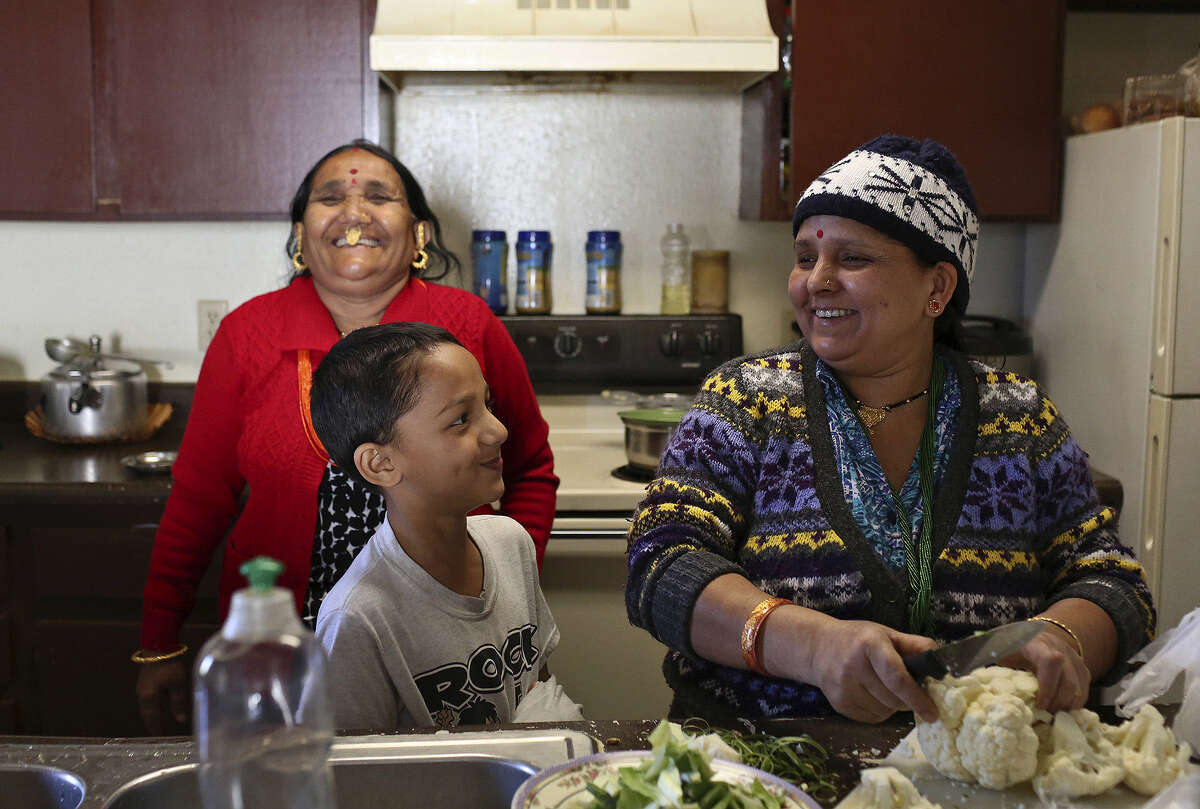 Kalu Biswa (right) cooks for her family including her mother-in-law, Deo Biswa (left), and son Youraj Biswa, 8, at their San Antonio apartment Thursday. The family, originally from Bhutan, moved to San Antonio more than two years ago from a refugee camp in Nepal. Kalu, her husband and their 19-year-old son, Tara Biswa, are now insured through the Affordable Care Act.