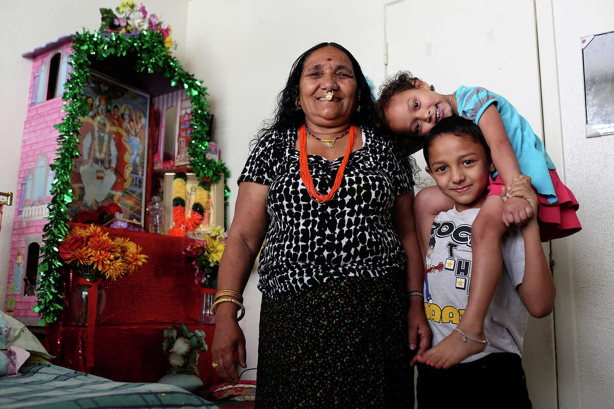 Deo Biswa, 71, stands with her grandchildren, Youraj Biswa, 8, and his cousin, Khusi Biswa, 4, at their apartment in San Antonio onThursday, March 13, 2014. The family, originally from Bhutan, moved to San Antonio over two years ago from a refugee camp in Nepal. The children were all born and raised in the refugee camp. Deo is covered by Medicare and the children are covered by Medicaid but Deo's son and daughter-in-law and their 19-year-old son are now insured through the Affordable Care Act.
