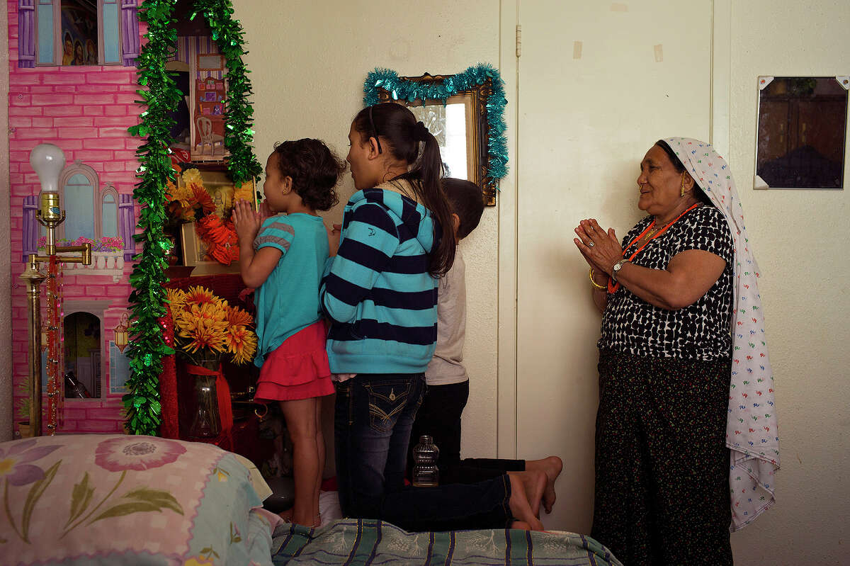 The Biswa family including Babita Biswa, 12, her grandmother, Deo Biswa, right, Babita's brother, Youraj Biswa, 8, and their cousin, Khusi Biswa, 4, pray at their apartment in San Antonio onThursday, March 13, 2014. The family, originally from Bhutan, moved to San Antonio over two years ago from a refugee camp in Nepal. Babita's parents and her older brother are now insured through the Affordable Care Act while the children are covered by Medicaid and their grandparents have Medicare.