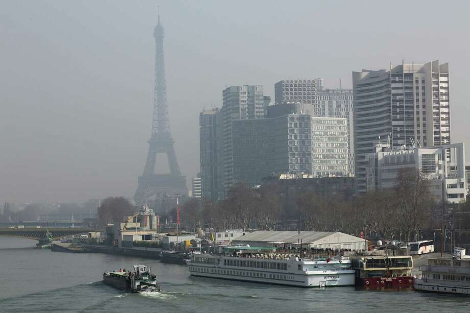 The Eiffel Tower and the Beaugrenelle district, right, are seen through the smog in Paris, Thursday March 13, 2014, as pollution over the French capital is at high levels. In an official effort intended to curb air pollution, Paris Town Hall announced that residential parking, will be free Thursday, to encourage drivers to leave their cars at home and take public transportation. (AP Photo/Remy de la Mauviniere) Photo: Remy De La Mauviniere, STF / AP