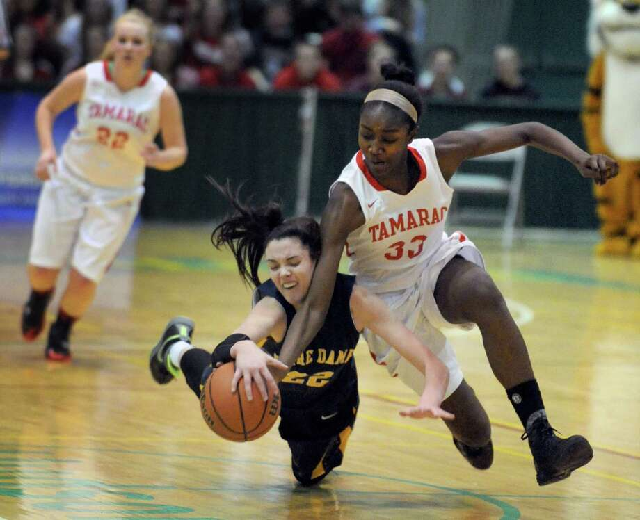 Tamarac's Adiya Henderson, right, and Notre Dame's Emily Durr battle for a loose ball during their Class B girls' basketball state semifinal game at HVCC on Friday March 14, 2014 in Troy, N.Y. Tamarac lost 55-69. (Michael P. Farrell/Times Union) Photo: Michael P. Farrell / 00026136A
