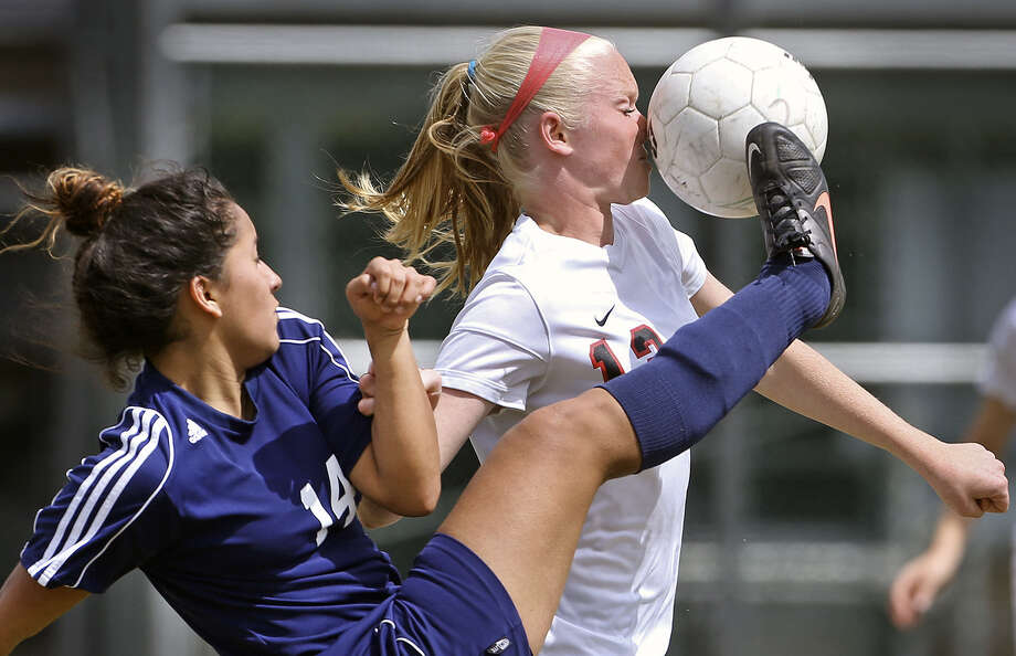 Roosevelt's Lisette Trujillo catches Churchill's Caroline Bowers with an inadvertent shot to the nose. The Rough Riders rallied from a 2-0 deficit and the game ended deadlocked, allowing Roosevelt to retain its playoff hopes. Photo: Tom Reel / San Antonio Express-News