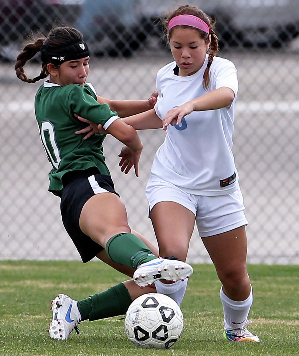 Reagan's Lina Fernandez stretches in for a tackle on Erika Palacios as Johnson plays Reagan in a 26-5A girls soccer match at Northeast Soccer Stadium on March 14, 2014.