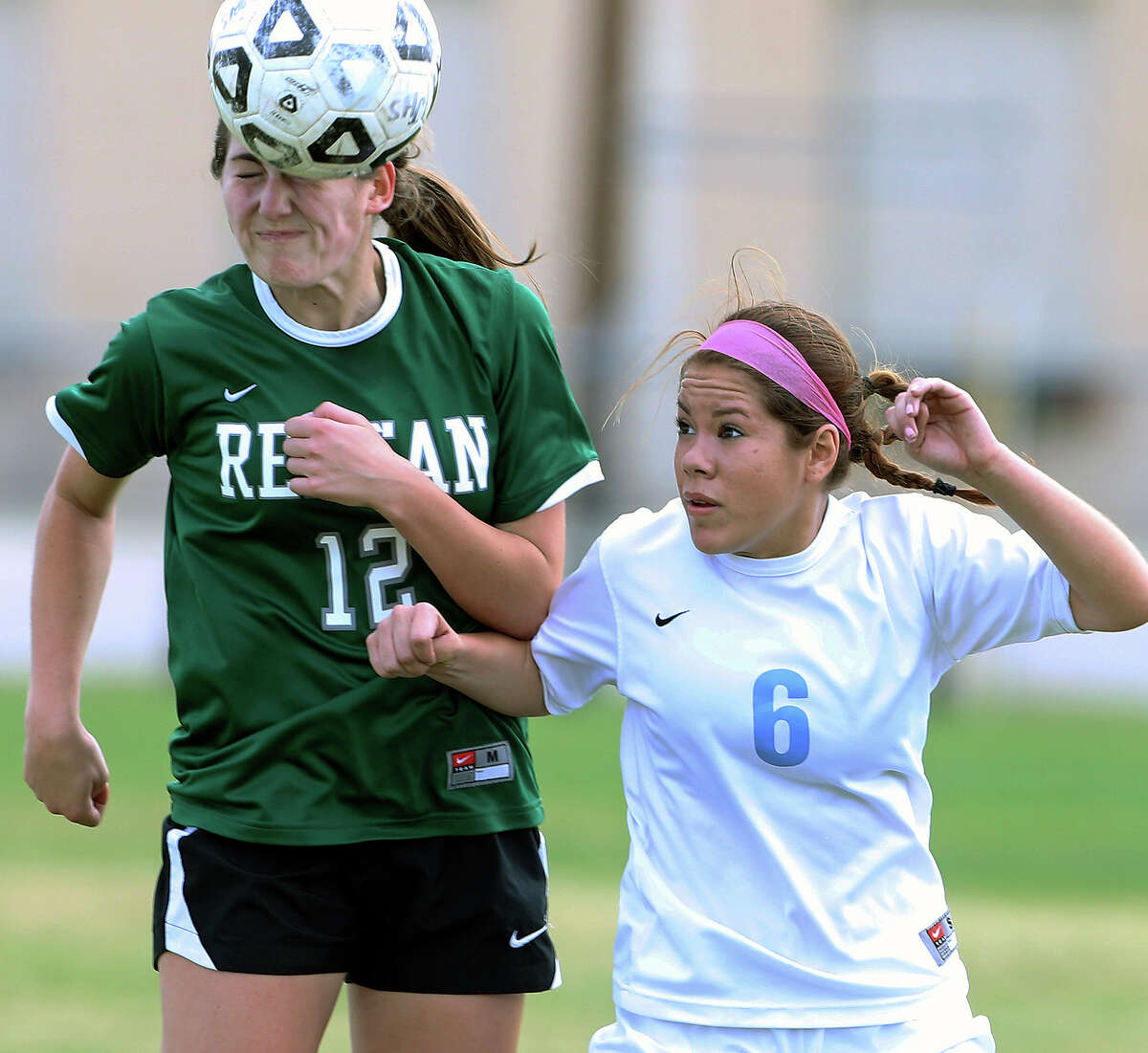 Reagan's Ashley Long bumps a pass in front of Erika Palacios as Johnson plays Reagan in a 26-5A girls soccer match at Northeast Soccer Stadium on March 14, 2014.