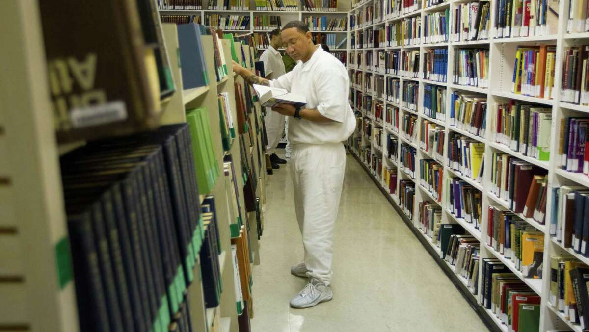 Student inmate Michael Smith looks for a book in the library Thursday, March 6, 2014, at the state prison system's Darrington Unit in Rosharon. Books are approved or denied by the Texas Department of Criminal Justice. The Texas Civil Rights Project calls many of the department's censorship decisions
