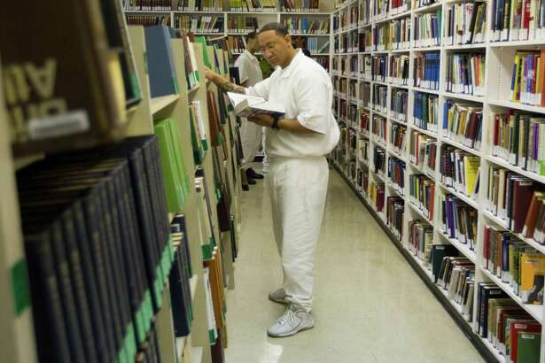 Student inmate Michael Smith looks for a book in the library Thursday March 6, 2014 at the Darrington Unit prison in Rosharon, TX.