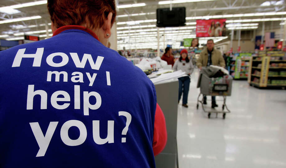 FILE - In this Sunday, Nov. 13, 2005, file photo, customers at a Wal-Mart store head to the checkout lines past a worker with the company's motto on the back of her vest, in Salt Lake City. With fewer middle-income jobs available, low-wage work is becoming a dead-end for more Wal-Mart employees. (AP Photo/Douglas C. Pizac, File) Photo: DOUGLAS C. PIZAC, STF / AP