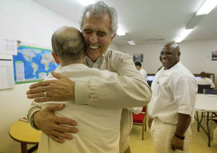 Grove Norwood, chairman of the Heart of Texas Foundation, hugs one of the Darrington Unit inmates enrolled in a course through Southwestern Baptist Theological Seminary. Photo: Billy Smith II, Staff / © 2014 Houston Chronicle