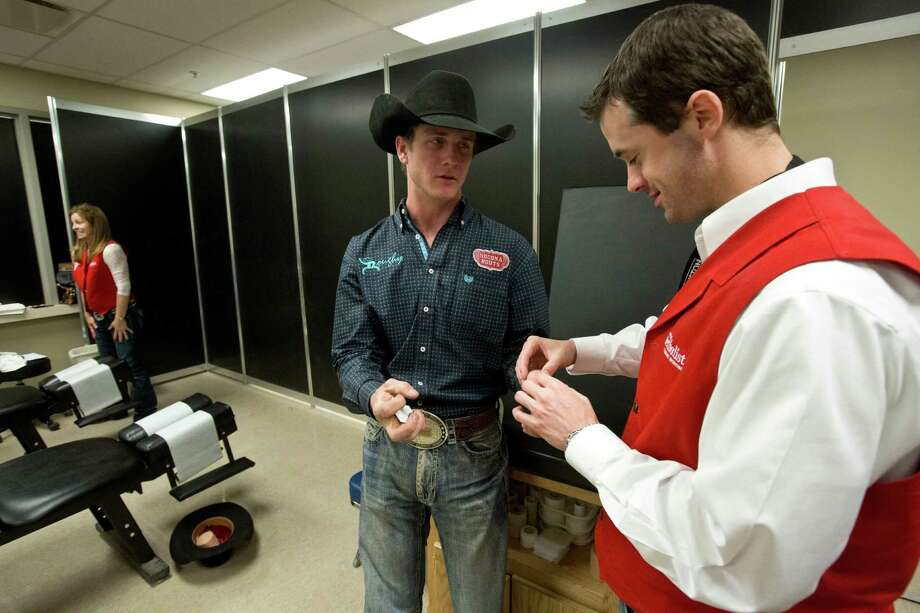 Doctor Joshua Harris, a orthopedic surgeon at Houston Methodist Orthopedics and Sports Medicine, cares for Sterling Crawley a saddle bronc riding athlete at the sports medicine clinic at the Rodeo Houston, Thursday, March 13, 2014, in Houston. Photo: Marie D. De Jesus, Houston Chronicle / © 2014 Houston Chronicle