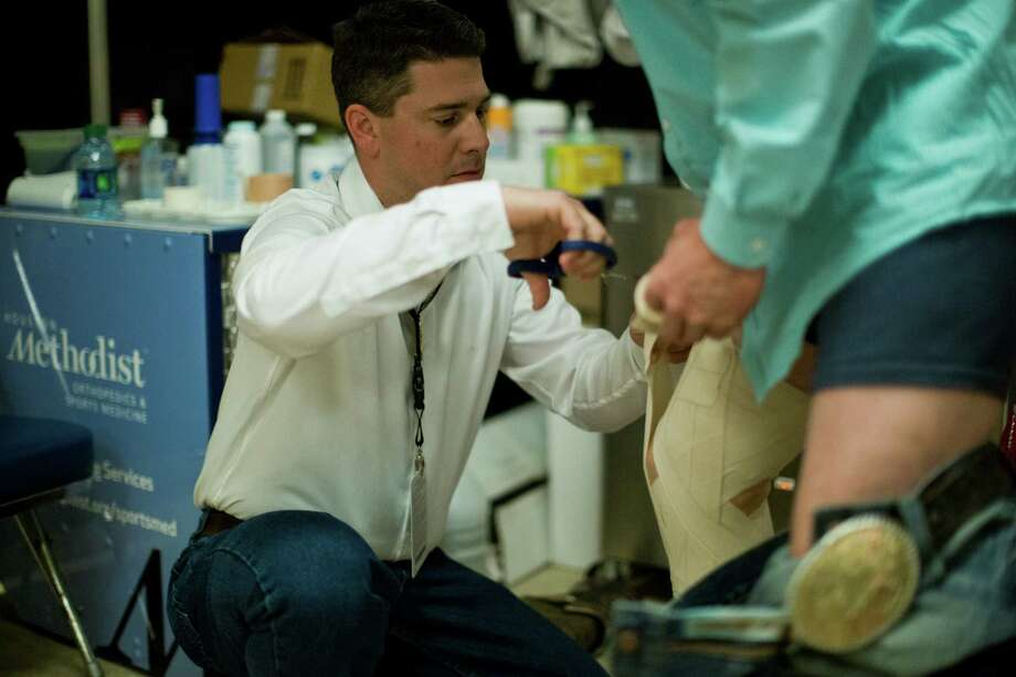 Chris Shaddock, left, an athletic trainer and part of the Rodeo Houston sports medicine committee, helps tie-down roping athlete Trent Creager  tape his knee before competition, Thursday, March 13, 2014, in Houston. Photo: Marie D. De Jesus, Houston Chronicle / © 2014 Houston Chronicle