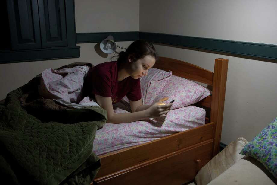 Jilly Dos Santos, who has campaigned for a later high school start time, replies to a text from her boyfriend just after her self-imposed bedtime of 11 p.m. Photo: DAN GILL, STR / NYTNS