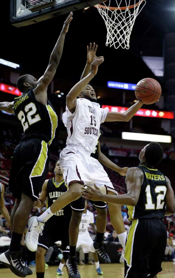 Texas Southern's D'Angelo Scott (15) shoots as Alabama State's Maurice Strong (22) and Jamel Waters (12) defend during the first half of an NCAA college basketball game in the semifinals of the Southwestern Athletic Conference tournament Friday, March 14, 2014, in Houston. Texas (AP Photo/David J. Phillip) Photo: David J. Phillip, Associated Press / AP