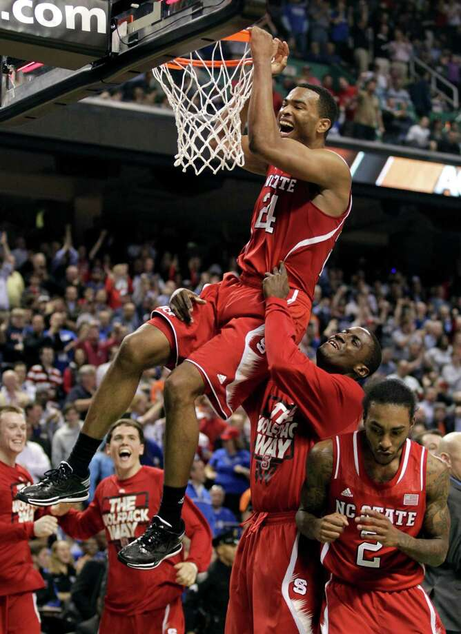 North Carolina State's T.J. Warren, top, is lifted by teammates as he grabs the goal to celebrate after a quarterfinal NCAA college basketball game against Syracuse at the Atlantic Coast Conference tournament in Greensboro, N.C., Friday, March 14, 2014. North Carolina State won 66-63. (AP Photo/Bob Leverone) ORG XMIT: NCCB153 Photo: Bob Leverone / FR170480 AP