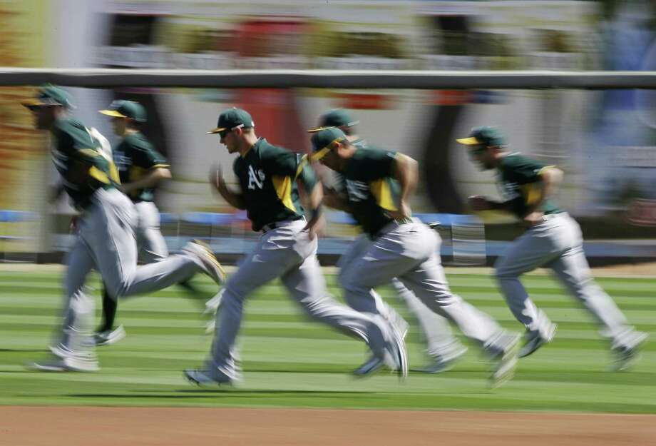 Members of the Oakland Athletics run before facing the Kansas City Royals on Friday in Surprise, Ariz. Photo: Darron Cummings / Associated Press / AP