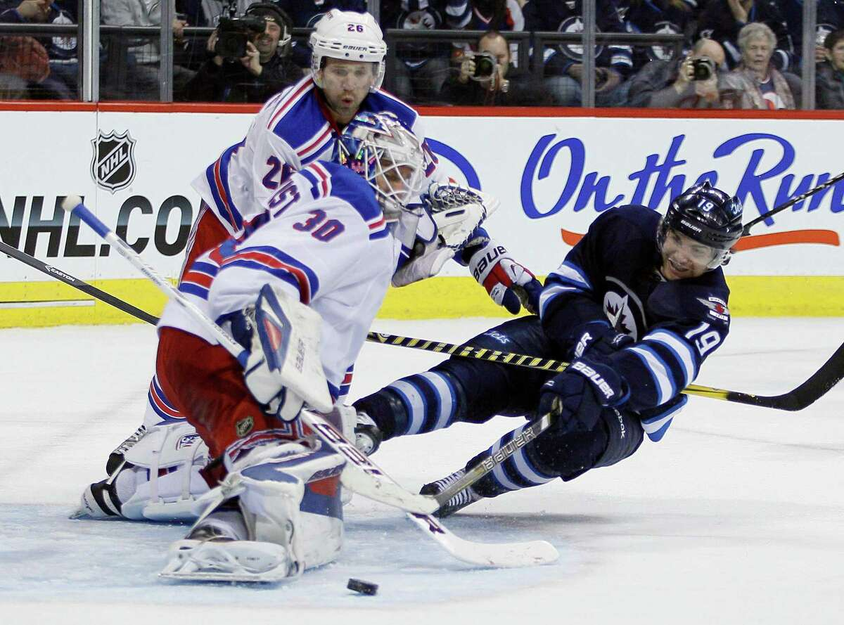 New York Rangers goaltender Henrik Lundqvist (30) saves a shot from Winnipeg Jets' Jim Slater (19) as Rangers' Martin St. Louis helps to defend during the second period of an NHL game in Winnipeg, Manitoba, Friday, March 14, 2014. (AP Photo/The Canadian Press, John Woods) ORG XMIT: JGW110