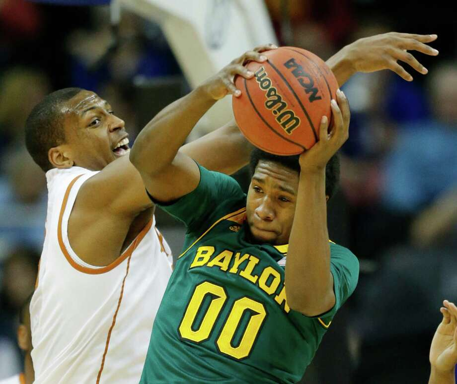 Baylor forward Royce O'Neale (00) rebounds against Texas forward Jonathan Holmes (10) during the first half of an NCAA college basketball game in the semifinals of the Big 12 Conference men's tournament in Kansas City, Mo., Friday, March 14, 2014. (AP Photo/Orlin Wagner) Photo: Orlin Wagner, STF / AP