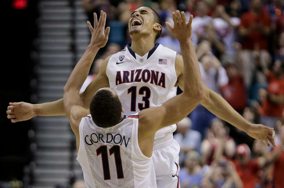 Nick Johnson (13) launches himself at Arizona teammate Aaron Gordon after launching a successful three-point shot. Photo: Julie Jacobson, Associated Press