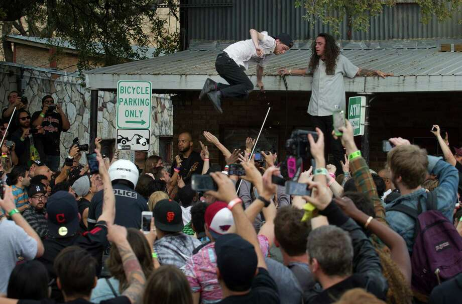 A fan jumps off the roof of the Beerland patio during a performance by the hardcore punk band Trash Talk at SXSW in Austin, Texas, on Friday March 14, 2014.   Several Austin police officers broke up the crowd and shut down the show after about 10 minutes.  (AP Photo/Austin American-Statesman, Jay Janner) AUSTIN CHRONICLE OUT, COMMUNITY IMPACT OUT; INTERNET AND TV MUST CREDIT PHOTOGRAPHER AND STATESMAN.COM; MAGS OUT Photo: Jay Janner, Associated Press / Austin American-Statesman