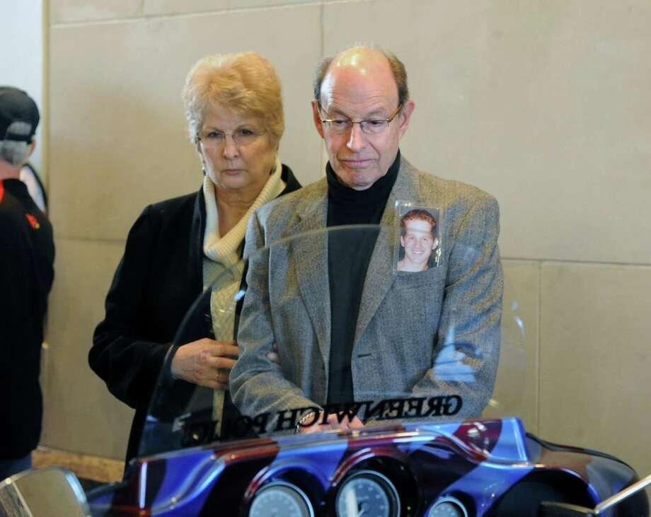 """Husband and wife, Paul and Sima Wachtler of Ramsey, N.J., during the Greenwich Police Department unveiling of their, """"Tribute to Heroes"""" motorcycle at Greenwich Police Headquarters in Greenwich, Conn., Saturday morning, March 15, 2014. The Wachtler's lost their son, Gregory on 9/11, he was 25. Gregory Wachtler's photo is visible in his father's pocket. According to Greenwich Police Sgt. John Slusarz, the Tribute motorcycle project was the collaboration of many officers within the department and  honors the heroes of the 911 terrorist attacks and the three Greenwich Police Officers who lost their lives in the line of duty. Photo: Bob Luckey / Greenwich Time"""