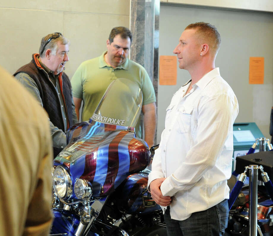 """Artist, Jamie Chasse of Southington, Conn., at right, who did the paint job for the Greenwich Police Department's, """"Tribute to Heroes"""" motorcycle, during the unveiling at Greenwich Police Headquarters in Greenwich, Conn., Saturday morning, March 15, 2014. According to Greenwich Police Sgt. John Slusarz, the Tribute motorcycle project was the collaboration of many officers within the department and  honors the heroes of the 911 terrorist attacks and the three Greenwich Police Officers who lost their lives in the line of duty. Photo: Bob Luckey / Greenwich Time"""