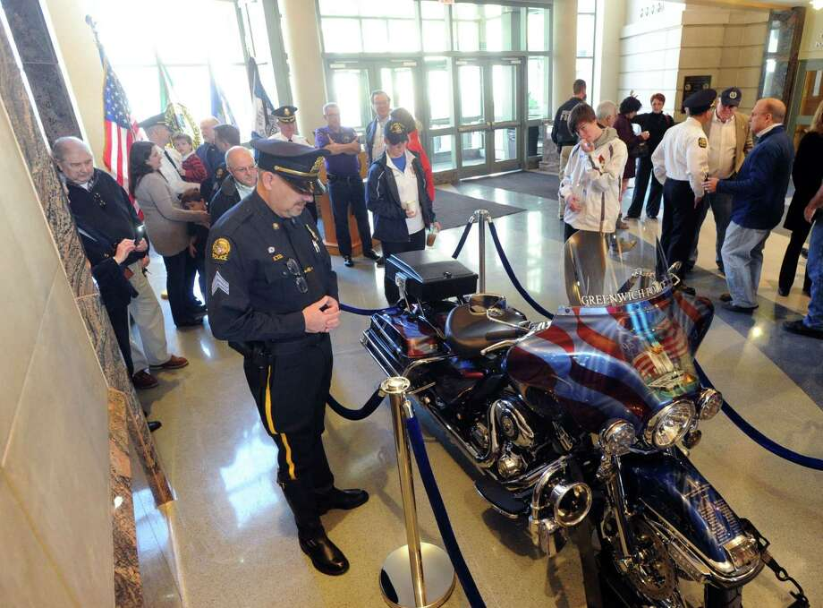 "The Greenwich Police Department unveiling of their, ""Tribute to Heroes"" motorcycle at Greenwich Police Headquarters in Greenwich, Conn., Saturday morning, March 15, 2014. According to Greenwich Police Sgt. John Slusarz, at left, the Tribute motorcycle project was the collaboration of many officers within the department and  honors the heroes of the 911 terrorist attacks and the three Greenwich Police Officers who lost their lives in the line of duty. Photo: Bob Luckey / Greenwich Time"