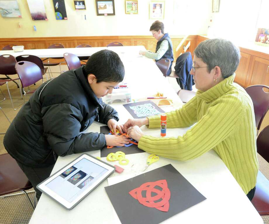 At left, Alexander Marroquin, 9, of Greenwich, makes a Celtic symbol during the Celtic knot and symbols arts & crafts workshop led by Byram Shubert Assistant Librarian, Andrea Vaz, right, at the Byram Shubert Library, Greenwich, Conn., Saturday, March 15, 2014. Vaz says the next monthly Arts & Crafts Workshop will be held at the library on Saturday, April 19, at 10:30 a.m., and will feature the art of making papier mache Easter eggs. Photo: Bob Luckey / Greenwich Time