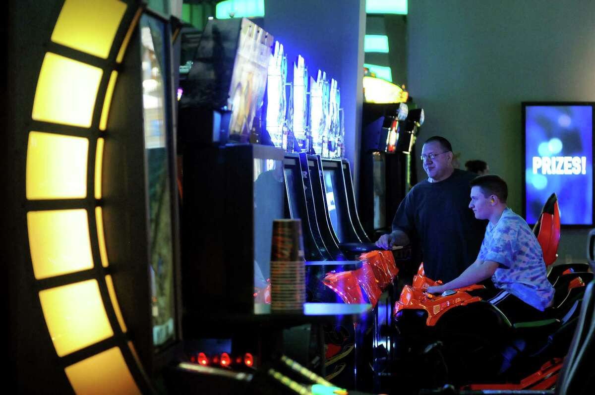Brian Pysher Sr. of Catskill, center, and his son Brian, 15, play a game in The Midway at Dave and Buster's restaurant on Friday, Oct. 18, 2013, at Crossgates Mall in Guilderland, N.Y. (Cindy Schultz / Times Union)
