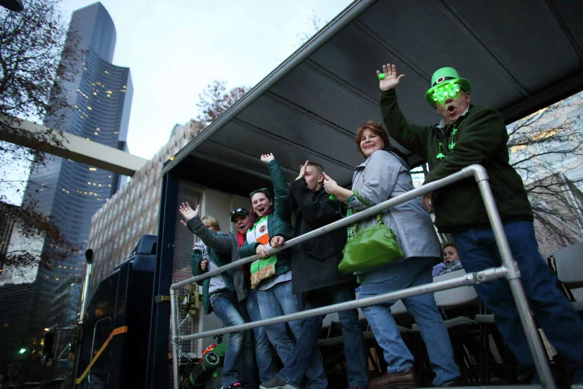 Participants wave from the bed of a semi truck participating in the parade during the 44th annual Laying O' The Green Stripe on 4th Avenue in downtown Seattle. A green stripe is painted along the street to mark the route of the St. Patrick's Day Parade. Photographed on Friday, March, 15, 2014.