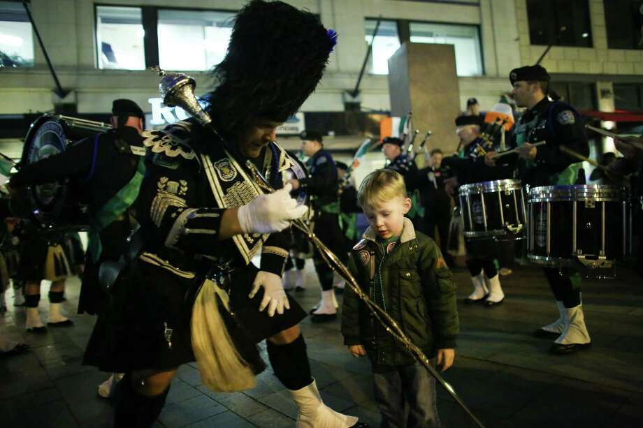 Jeremiah Green, 3, is offered a baton by a member of the Seattle Police Department Pipes and Drum Corps as they play during the 44th annual Laying O' The Green Stripe on 4th Avenue in downtown Seattle. A green stripe is painted along the street to mark the route of the St. Patrick's Day Parade. Photographed on Friday, March, 15, 2014. Photo: JOSHUA TRUJILLO, SEATTLEPI.COM / SEATTLEPI.COM