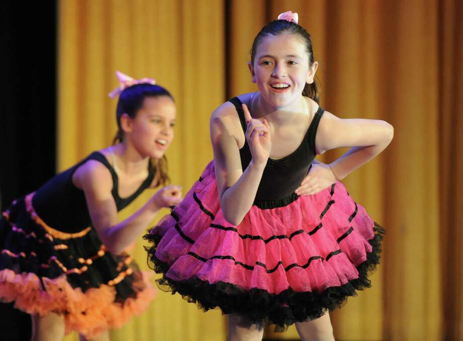 Nine-year-olds Katie Daoust, left, and Norah Hampford, of Connecticut Dance, perform a dance routine at the 6th Annual Symphony of Smiles fundraiser for Brady's Smile at Edmond Town Hall in Newtown, Conn. Saturday, March 15, 2014.  Brady's Smile, Inc. is a children's-based charitable organization created by Annie and Matt Hinton, of Fairfield, in memory of their son, Brady, who died on his second birthday.  The organization seeks to make life easier in the pediatric and newborn intensive care units for patients and families.  Brady's Smile currently serves 15 hospitals across seven states and has donated over $100,000 to hospitals in Connecticut alone.  The Symphony of Smiles events featured singing and dancing from Connecticut Dance and other individuals and groups. Photo: Tyler Sizemore / The News-Times