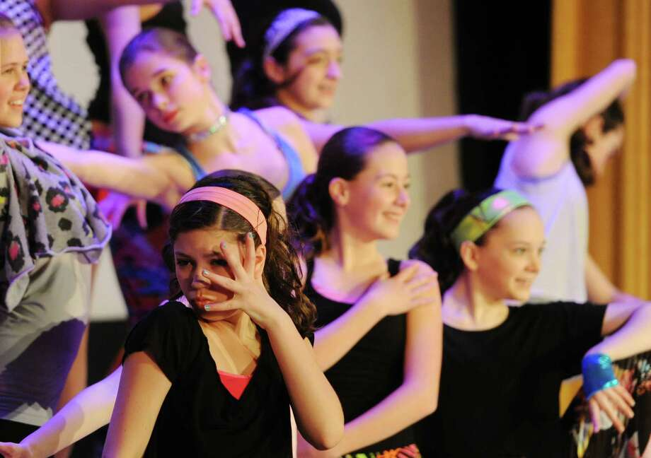 Megan Kubicko, bottom left, 13, and others from Connecticut Dance perform a dance routine at the 6th Annual Symphony of Smiles fundraiser for Brady's Smile at Edmond Town Hall in Newtown, Conn. Saturday, March 15, 2014.  Brady's Smile, Inc. is a children's-based charitable organization created by Annie and Matt Hinton, of Fairfield, in memory of their son, Brady, who died on his second birthday.  The organization seeks to make life easier in the pediatric and newborn intensive care units for patients and families.  Brady's Smile currently serves 15 hospitals across seven states and has donated over $100,000 to hospitals in Connecticut alone.  The Symphony of Smiles events featured singing and dancing from Connecticut Dance and other individuals and groups. Photo: Tyler Sizemore / The News-Times