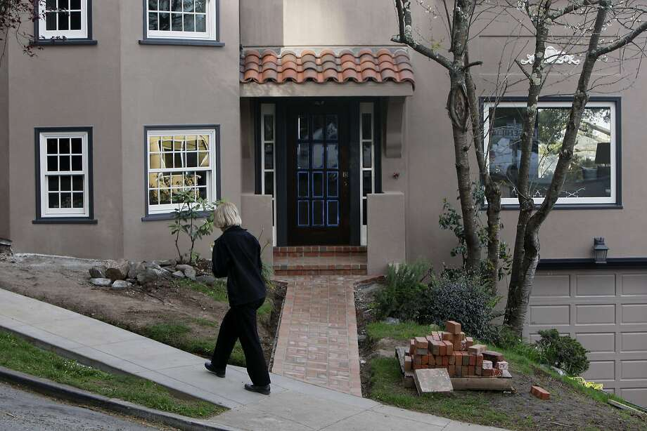 A woman walks past a house at the corner of Garcia Avenue and Edgehill Way in Forest Hill Extension on March 14, 2014 in San Francisco, Calif. Photo: Codi Mills, The Chronicle