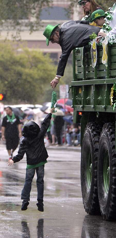 Bill Ensel right, tosses beads to six-year-old Sean Doyle left, during the 55th annual St. Patrick's parade which salutes Houston's first responders this year Saturday, March 15, 2014, in Houston. ( James Nielsen / Houston Chronicle ) Photo: Houston Chronicle