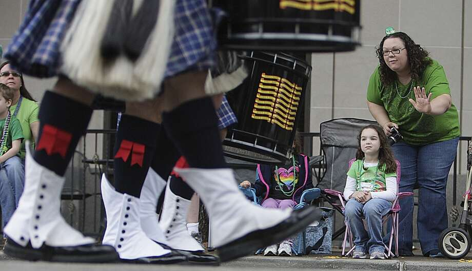 Five-year-old Allie Hylan left, and her mother Stephanie Hylan watch as the bag pipers pass during the 55th annual St. Patrick's parade which salutes Houston's first responders this year Saturday, March 15, 2014, in Houston. ( James Nielsen / Houston Chronicle ) Photo: Houston Chronicle
