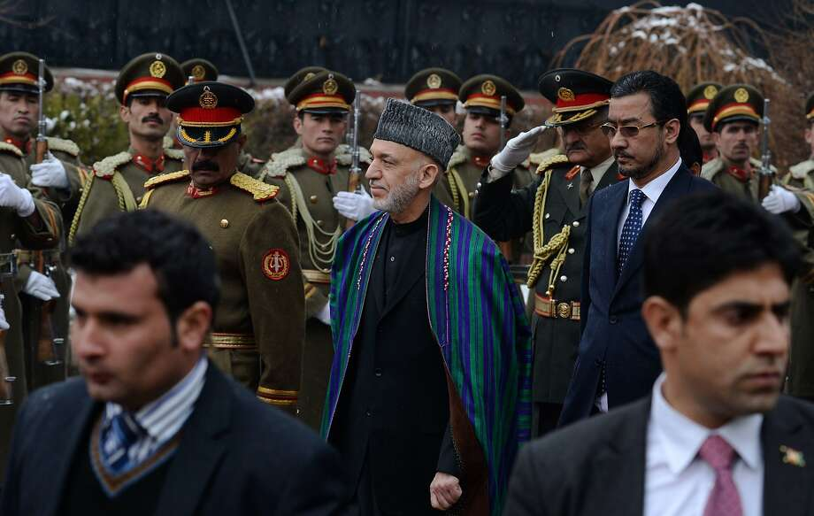 Afghan President Hamid Karzai (center) arrives in parliament in Kabul on Saturday. Karzai has expressed an increasingly strong desire for U.S. troops to withdraw from his nation. Photo: Wakil Kohsar, AFP/Getty Images