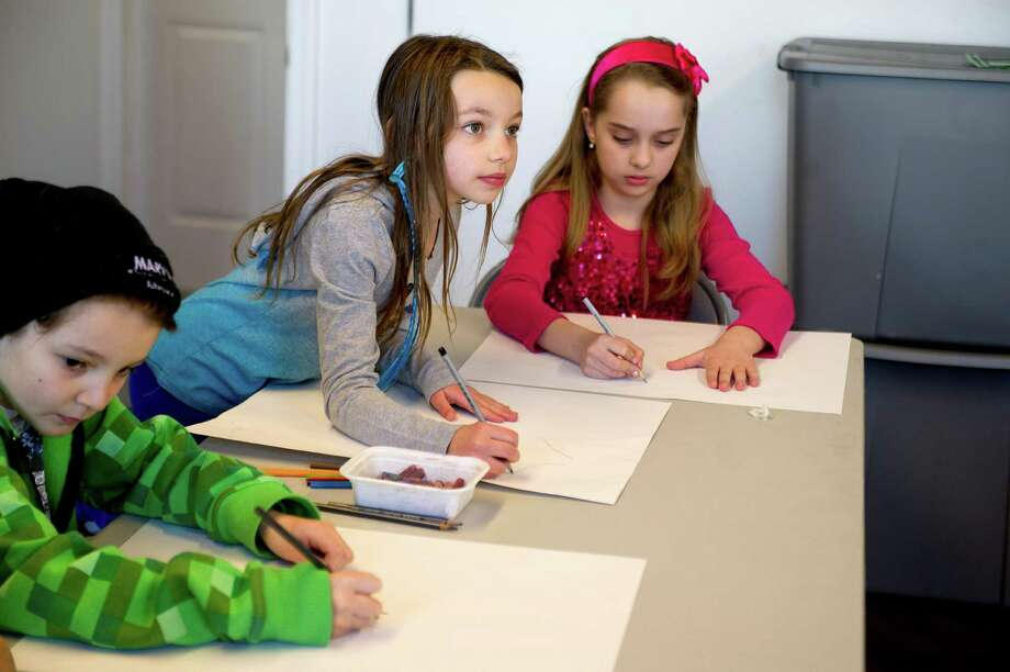 Melia Peragine, 8, center, and Lily Gillespie, 8, right, draw the cowardly lion and the tin man from The Wizard of Oz by looking up at actors from Curtain Call dressed in character during the Loft Artists Association's free Draw On workshop on Saturday, March 15, 2014. Photo: Lindsay Perry / Stamford Advocate