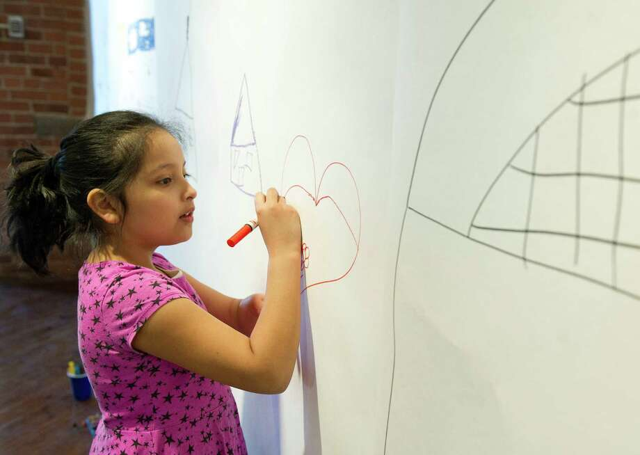 Genesis Mendez, 8, draws on a wall during the Loft Artists Association's free Draw On workshop on Saturday, March 15, 2014. Photo: Lindsay Perry / Stamford Advocate