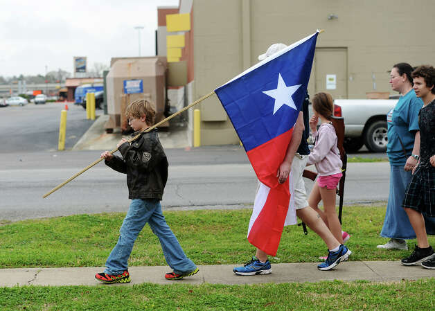 Ryley Franklin, 13, carries a Texas state flag during Saturday's rally. Come and Take It Beaumont held a march down Dowlen Road on Saturday. The participants carried long arms as well as Texas and United States flags from Sertinos Cafe to Lowes.